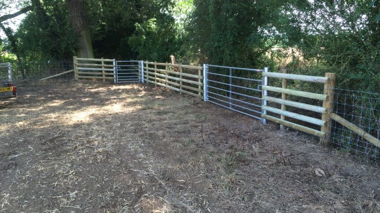 round post and rail fencing with metal gates